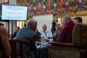 Переводчик Его Святейшества Далай-ламы Тхуптен Джинпа помогает Его Святейшеству объяснить значение одного из слайдов презентации во время первого дня диалога с китайскими квантовыми физиками. Дхарамсала, Индия. 1 ноября 2018 г. Фото: дост. Тензин Джампхел.