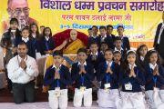 Его Святейшество Далай-лама фотографируется с группой школьников из соседних деревень, прочитавших молитвы на языке пали в начале первого дня трехдневных учений, организованных по просьбе Молодежного буддийского общества Индии. Санкиса, штат Уттар-Прадеш, Индия. 3 декабря 2018 г. Фото: Лобсанг Церинг.